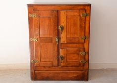 A vintage oak ice box. The three zinc-lined insulated compartments held a block of ice and perishable food. This type of icebox was popular from the mid-19th century to the 1930s when electric cool...