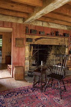 The keeping room ~ A walk-in fireplace with 18thC ironware, exposed ceiling joists, a C1760-68 highback Windsor armchair beside a joined stool, and an early oriental rug on the floor.