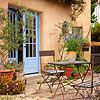 The house color, the garden foliage, the iron bistro table and chairs....perfect backyard spot to recreate.