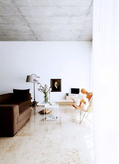 Bright, minimal open plan living room design with concrete ceiling and leather butterfly chairs.
