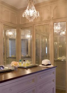 chic walk-in closet design with crystal chandelier, white cabinets with mirrored doors and custom island.