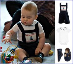 """For his first official appearance, George wore navy blue """"Sailboat Smocked Dungarees"""" by Rachel Riley UK with a white Peter Pan collar """"Milo"""" body suit by Chelsea Clothing Co. Baby George finished his outfit with """"Alex Pre-Walker"""" shoes in navy leather by Early Days."""