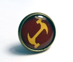 A bronze pin/tie tack, with a 12mm setting. Show your love for The Simpsons with this tiny pin! Let everyone know, in a subtle, secret way, that youre a Stonecutter! (Ssshhut up...) Perfect for getting free candy from a vending machine. (NOTE: no you wont get any free candy. But youll be fine because you have a great looking pin on).