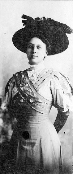 "Almost full-length portrait of Bess Wallace, wearing a large picture hat and glasses. Photo is mounted on a card, with autograph on the card: ""Most Sincerely, Bessie '08."""