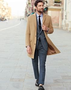Shop this look on Lookastic: http://lookastic.com/men/looks/dress-shirt-and-tie-and-suit-and-overcoat-and-derby-shoes/3864 — Light Blue Dress Shirt — Black Tie — Charcoal Suit — Camel Overcoat — Black Leather Derby Shoes
