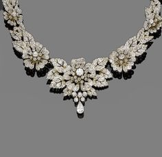 A diamond necklace/tiara combination, circa 1890  Composed of graduating pierced flowerheads and leaves, the largest to the centre, set throughout with old brilliant, single and rose-cut diamonds, with a pear-shaped diamond drop, mounted in silver and gold, tiara frame deficient, central brooch fitting provided, diamonds approx. 5.60ct total, length 37.5cm, fitted case by Nathan & Co, Birmingham