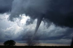 A tornado near Anadarko, Oklahoma. The funnel is the thin tube reaching from the cloud to the ground. The lower part of this tornado is surrounded by a translucent dust cloud, kicked up by the tornado's strong winds at the surface. The wind of the tornado has a much wider radius than the funnel itself.