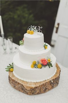 simple white wedding cake with tandem bike cake topper and rustic log cake stand | photo: www.sarakbyrne.com