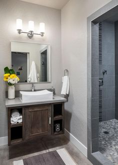A rustic-look floating vanity opens up floor space and visually expands this neutral contemporary bathroom. The gray-tiled shower with pebble mosaic floor adds to the contemporary feel of the space.