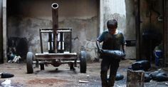 A Syrian child carries a mortar shell in Aleppo, Syria.