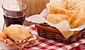Le pizze fritte, conosciute come pizzelle, sono una ricetta tipica del napoletano. Si tratta di pasta fritta e condita con pomodoro e formaggio.