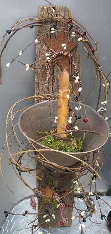 old funnel wired to piece of old wood ..then wrapped with pip berry garland..and battery operated candle
