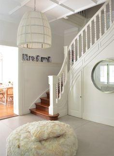La entrada de la casa es serena y luminosa y funciona como un pulmón que conecta los diferentes ambientes. La baranda de la escalera original se pintó de blanco para alivianar su estilo, y se conservó el techo con cuarterones.