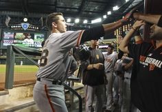 Buster Posey #28 of the San Francisco Giants is congratulated by teammates as he returns to the dugout following his solo home run against the Arizona Diamondbacks during the fourth inning of a MLB game at Chase Field on September 16, 2014 in Phoenix, Arizona. (September 15, 2014 - Source: Ralph Freso/Getty Images North America)