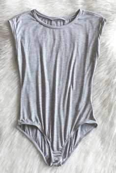 Basic jersey knit rolled up cap sleeve bodysuit. Looks amazing paired with classic denim jeans or shorts! Made in the USA with lightweight and stretchy material. Button snap crotch closure. Available