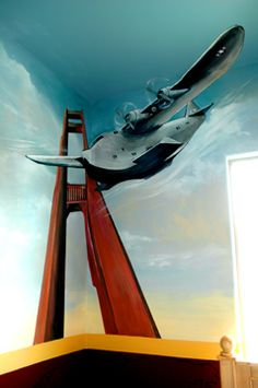 For those that love travel, the Golden Gate bridge in one corner of the room and the Eiffel tower in the other. Real plane parts accessorize the mural. . here one of the wings is real and extends out of the wall and in the other corner, real propellers were added to the wing and move when the air condition hits.  Artwork done by Carmen Benoit of Carmen Illustrates.