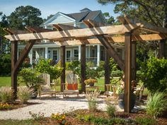 """A pea gravel surface outlines this outdoor living area while a pergola offers visual interest and a support system for growing muscadine grapevines, which will eventually create three living walls. """"You'll have a view of water, but all that plant matter will make this area cooler and more shaded,"""" says project manager Dylan Eastman."""