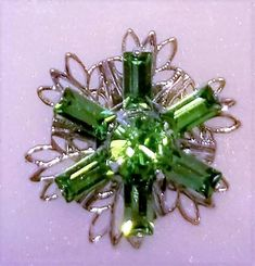 E-179, $4.25, A Beautiful Silver Toned Flower with Green Swarovski Crystals in the Center