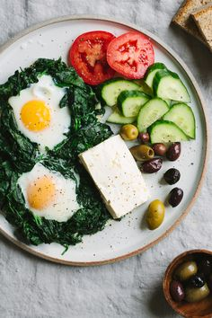 Turkish Baked Eggs- two eggs oven-baked sunny side-up, nestled in a bed of sautéed spinach with hints of oregano, and served alongside tomatoes, cucumbers,
