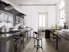 stainless steel kitchen + whitewashed stone walls + white curtains separating the kitchen