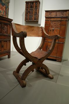 This sedia Dantesca dates from the 15th century ard originates from Spain where it  is called sillon de cadera. The chair is made form walnut with intarsia from ivory, ebony, and pearl-shell.  The seating is made from leather, however not original, and nailed to the chair. The chair measures 71 x 69 x 50 cm.