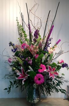 Gerbera daisies, liatris, snap dragons, make for a stunning gardeny look. Accented  with tall curly willow and arranged in a trendy silver mercury vase.Twigs & Vines Floral Original