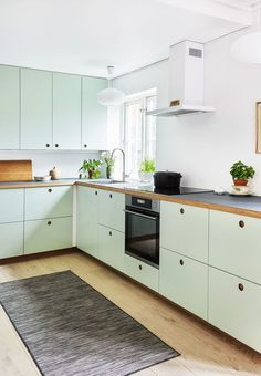 Modern kitchen from Ikea with mint green cabinetry and drawer fronts and round integrated cut outs for handles.
