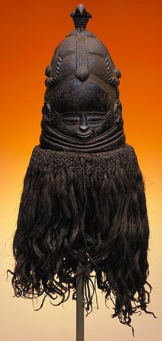 Africa, Sierra Leone  Sande Society Mask, 20th century  wood, raffia.  This mask from the Sande Society in Sierra Leone was worn by a mature woman as part of an initiation ceremony for young girls entering adulthood. The mask represents the ideal of womanhood and feminine beauty among Mende women.