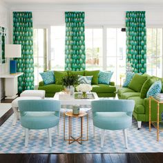 Cheerful shades of blue meet energetic greens in the peacock feather–print curtains by Peter Dunham in this living room, harmonizing the two distinct hues, while white stools and brass side tables throughout keep the room's focus centered on the color pairing.