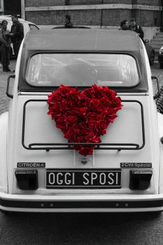 A WHITE CAR WITH A BLACK ROOF HAVING A POP OF COLOR WITH A BIG RED HEART !!!!