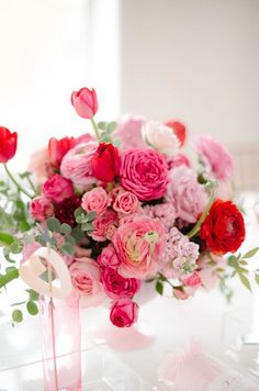 Varying shades of pink add depth to this centerpiece of ranunculus, tulips and pink sweet peas. Wedding Flowers, Wedding Décor, Ranunculus, Wedding Centerpieces