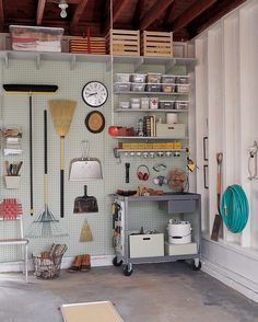 A pegboard organizes tools and brooms, while a metal cart serves as a mobile workbench. Adjustable shelves display an assortment of containers, including a painted wooden box that stores glue; glass jars contain small hardware. And the pan of sand on the floor catches oil drips from the car.