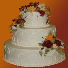 This 3 tiered buttercream cake is perfect for any fall themed wedding.  The  icing  flowers are done in burgundy, peach and burnt orange . Sage green leaves finish off this seasonal cake.