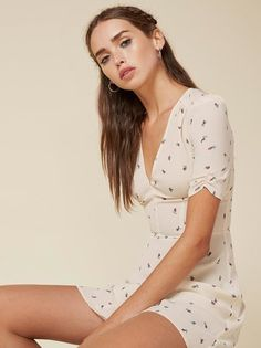 V cute. This is a short sleeve, fit and flare dress with a deep v neckline and puff shoulder sleeve.