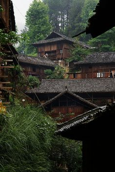 Men working on the roof of traditional Miao wood houses, Xijiang village, Guizhou, China