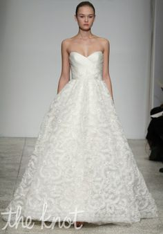 Gown features embroidery, ruching, and floral corsage at waist.