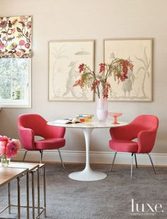 Dressed with a bright coral-pink fabric, Saarinen chairs pull up to a marble-topped Saarinen table, both by Knoll and purchased from Jules Seltzer Associates, to provide a spot for projects. The artwork is from Hollyhock