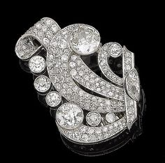A diamond clip brooch, circa 1930 Of scrolling design, set throughout with old brilliant, single-cut and pear-shaped diamonds, diamonds approx. 8.20cts total, converted from a clasp, length 3.6cm