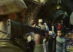Israeli Soldier points gun at young Palestinian boy at a market in Al Khalil(Hebron),Palestine.