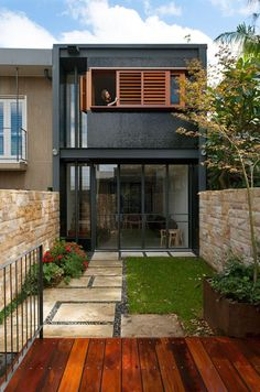 Wooden shutters contrast the black facade of this Australian home.