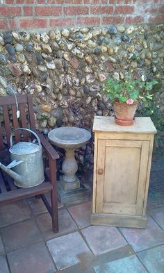 Vintage bird bath, watering can and bench with flint wall.