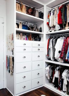 White walk-in closet is fitted with The Container Store 11-Peg Acrylic Necklace Wall Racks mounted to the side of white stacked bag shelves fixed above a white built-in dresser finished with polished nickel cup pulls.
