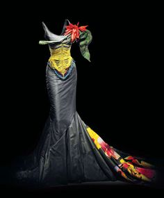 John Galliano for Dior, 1997​​.  Kitu S-line gown in black silk taffeta with fishtail train. Inspired by the corsets worn by warriors of the Dinka tribe in East Africa and the hourglass silhouette of Belle Epoque, this dress features a Masai-style beaded corset and choker, as well as painted tropical flowers in organza. ​