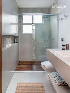 Reforma em apartamento deixa a cozinha aberta para a sala - Casa | Exibindo o mesmo revestimento cimentício, o banheiro ganhou deck de cumaru e pastilhas cerâmicas (Jatobá) no boxe.