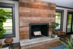 The space, now merged with the main living room, now has an updated fireplace with a surround clad in reclaimed wood and concrete hearth. New concrete had to be poured in this space to bring all floors of the living space to a uniform level.
