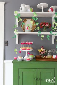 Tropical paradise party decor: flamingo cake toppers, sunglasses toothpicks, beach balls, paper palm tree garland.