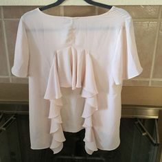 Backless ruffle top Really cute top that is backless and accented by Ruffles. Last pic shows me pointing to a really small spot. Hard to see but want you to be aware. Polyester fabric. Size large. Color is Nude with a hint of pink. Forever 21 Tops Blouses
