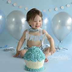 Blue and silver boys first birthday cake smash photo shoot featuring our 'ONE' cake topper and custom silver glitter circle garland