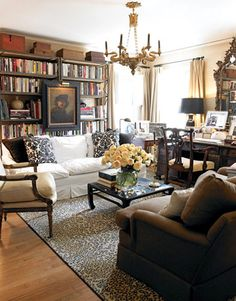 Small space living - multipurpose den  living room.   Neutral upholstery and curtains, desk  bookcases.   Dallas Home of Craig Schumacher and Philip Kirk - House Beautiful