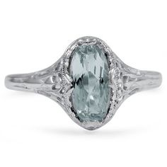 oval aquamarine rests atop an intricate white gold design in this feminine ring from the Edwardian era